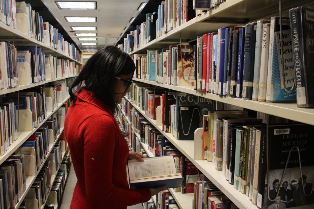Woman in library aisle looking at book.