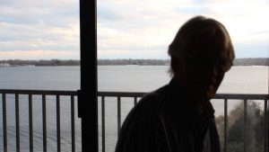 Darkened image of man on balcony near lake.