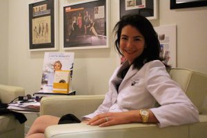 Woman in medical coat sitting in front of framed magazine posters.