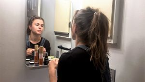 Woman using skincare products looking into mirror.