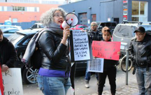 Woman with microphone surrounded by people holding signs.