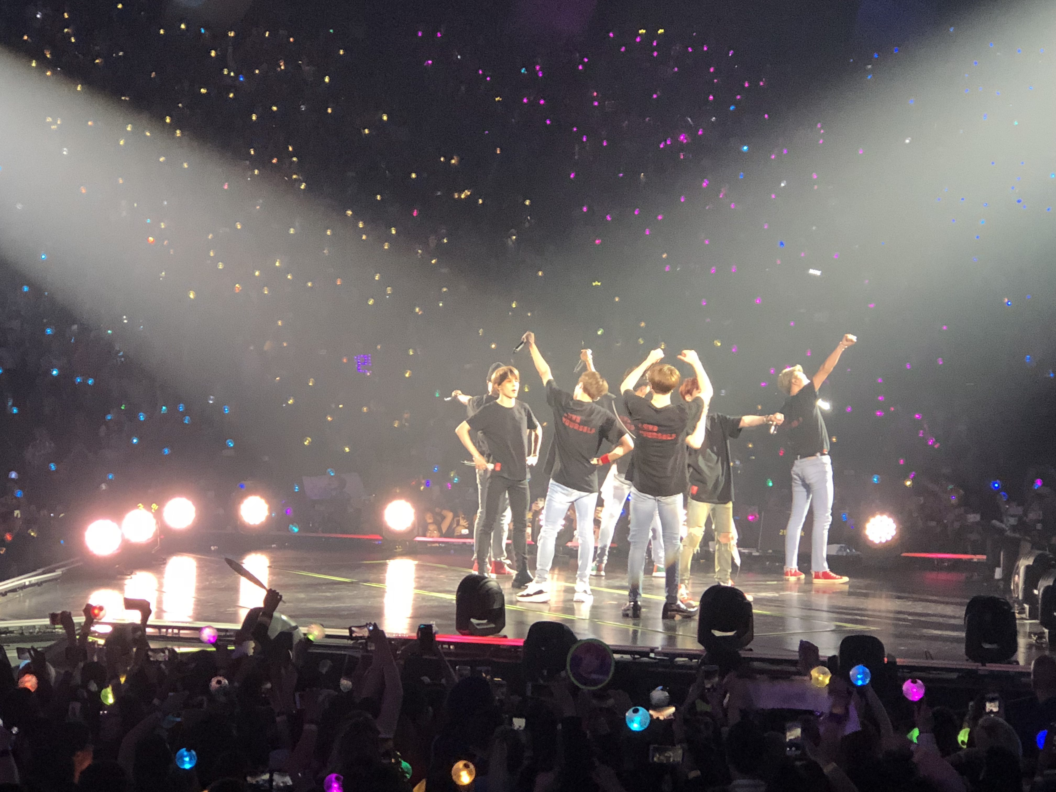 Band BTS on stage waving to fans in audience.