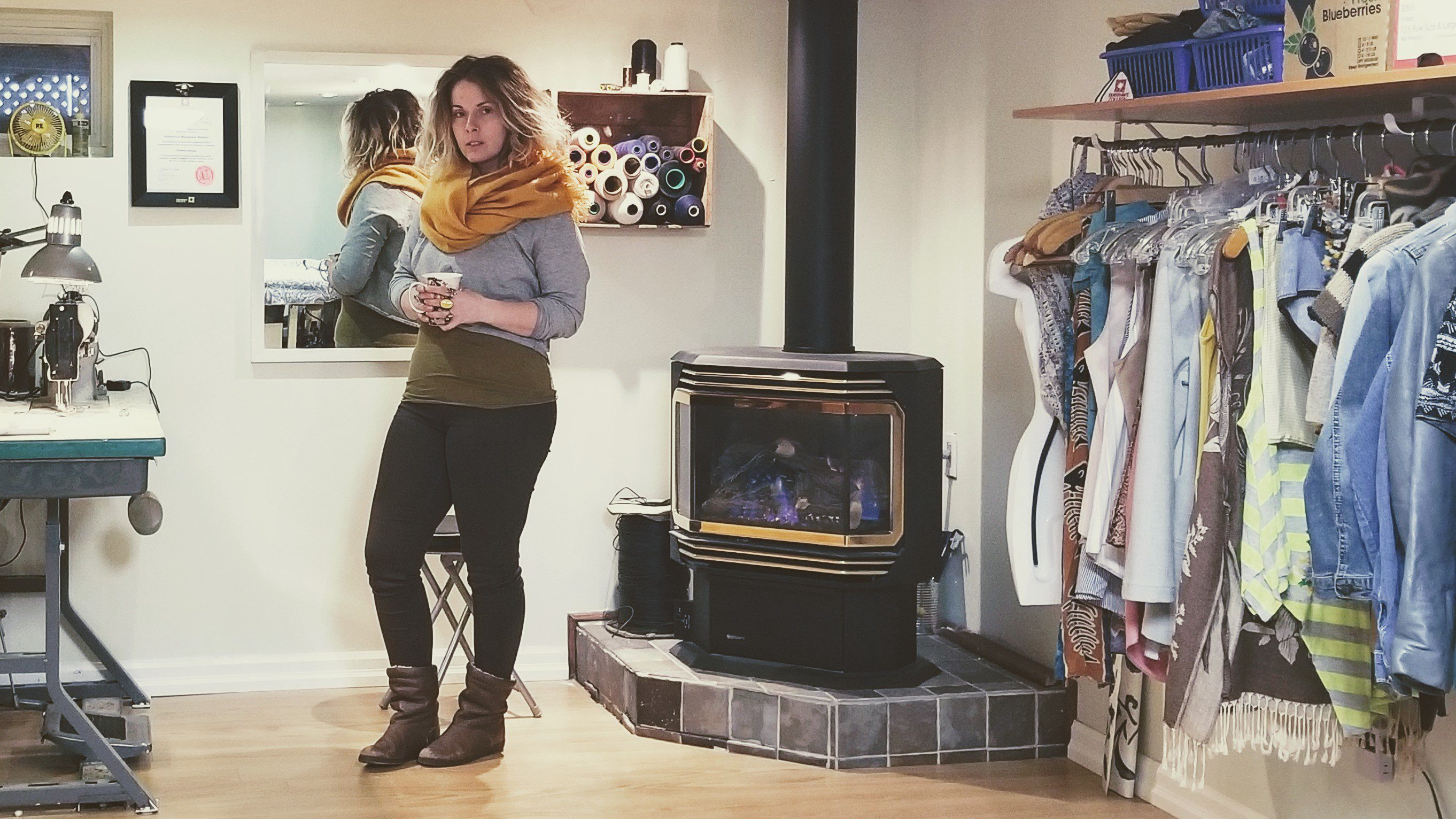 Woman standing next to fire place and large rack of clothing.