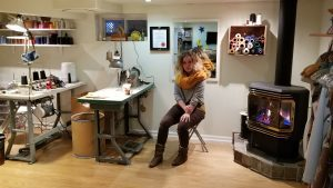 Woman sitting next to fire place and sewing workshop.