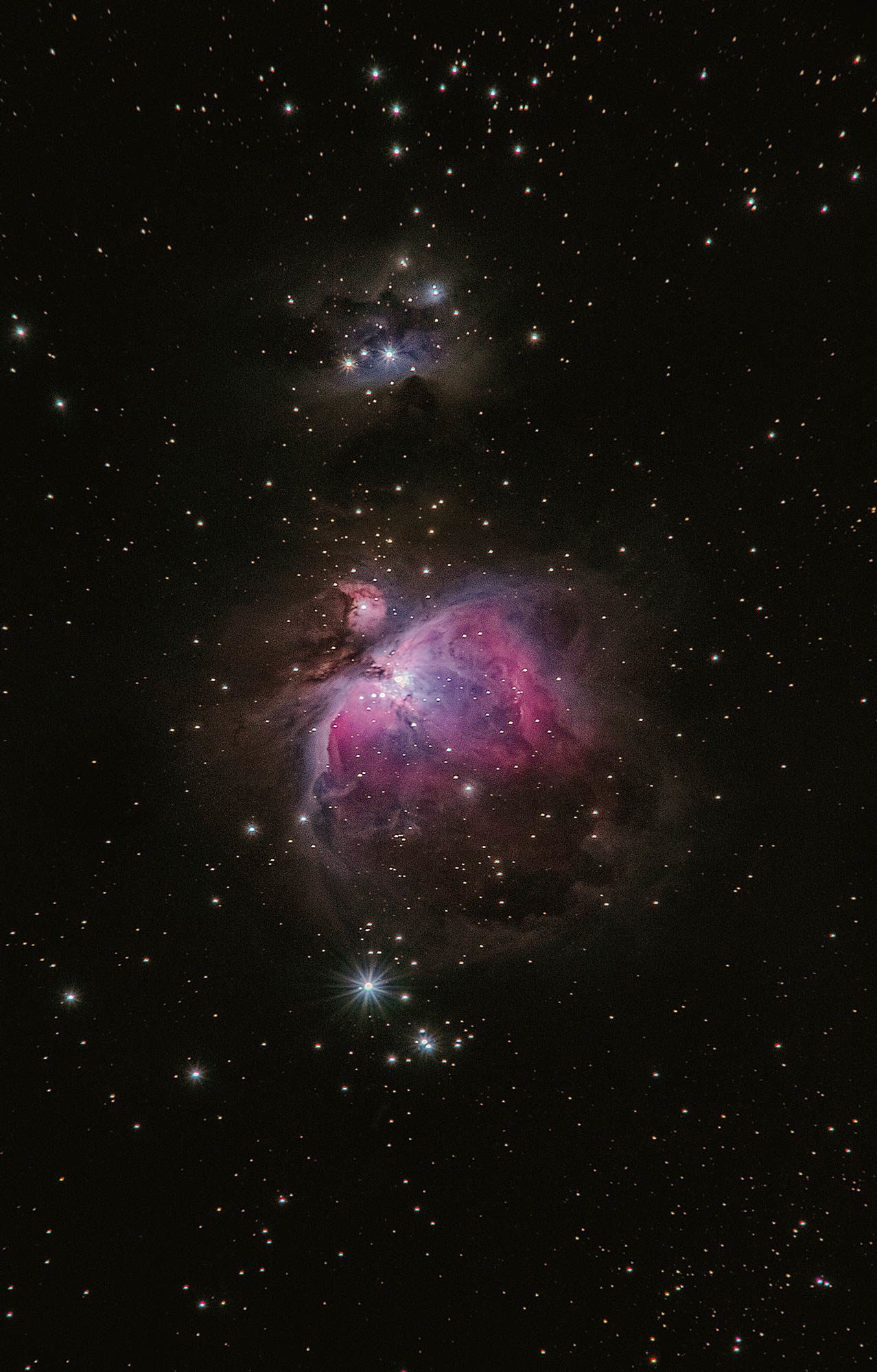 View of outer space of stars and pink nebula.