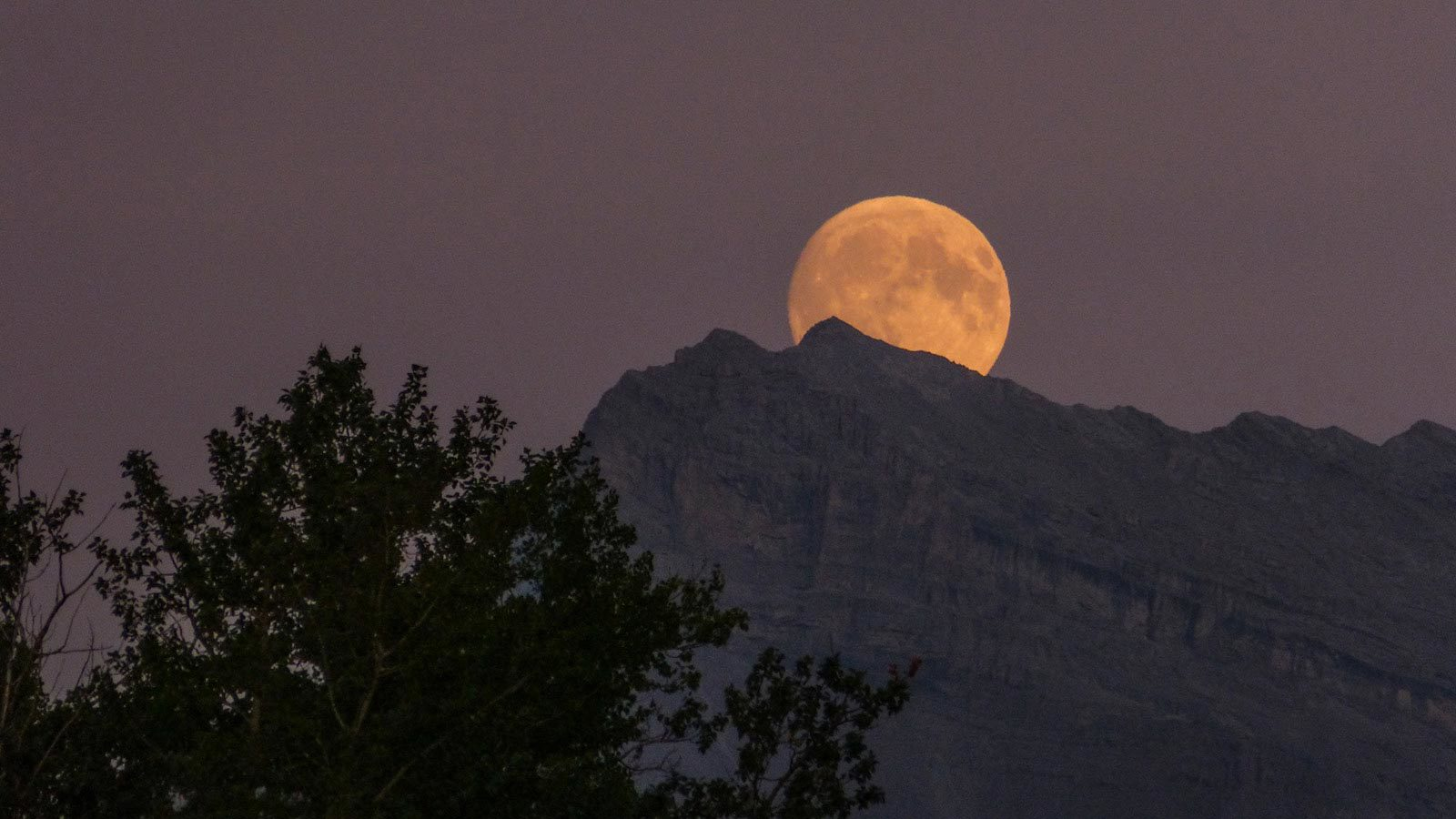 View of large moon behind large mountain.