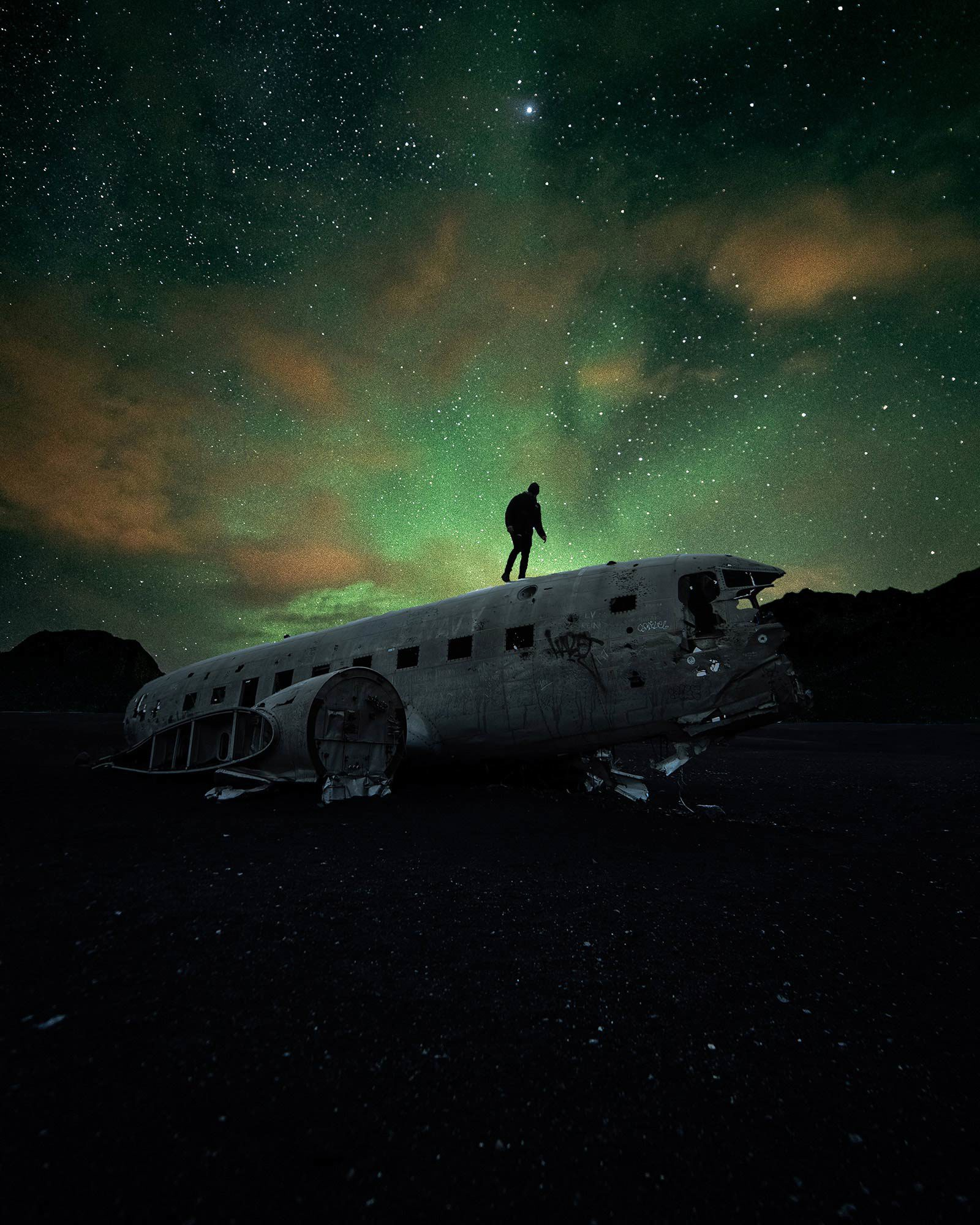 Person walking on crashed airplane under green starry sky.
