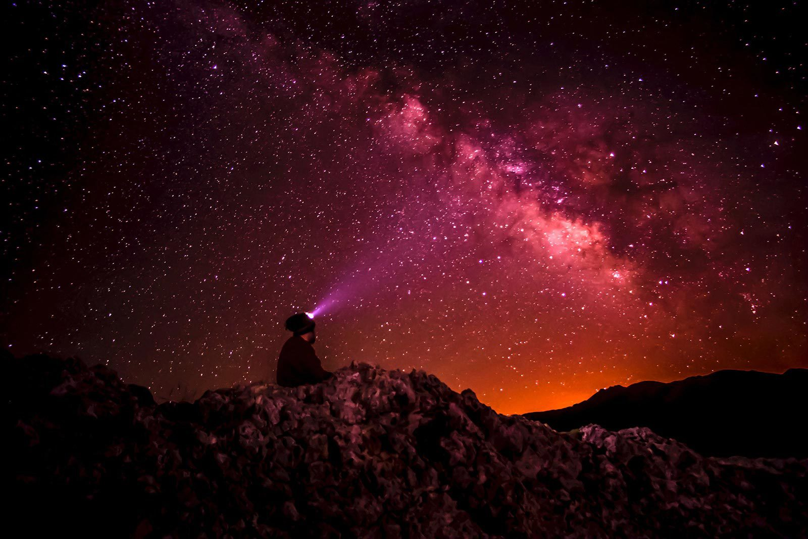 Person with headlamp sitting on mountain looking at red and pink sky with stars.