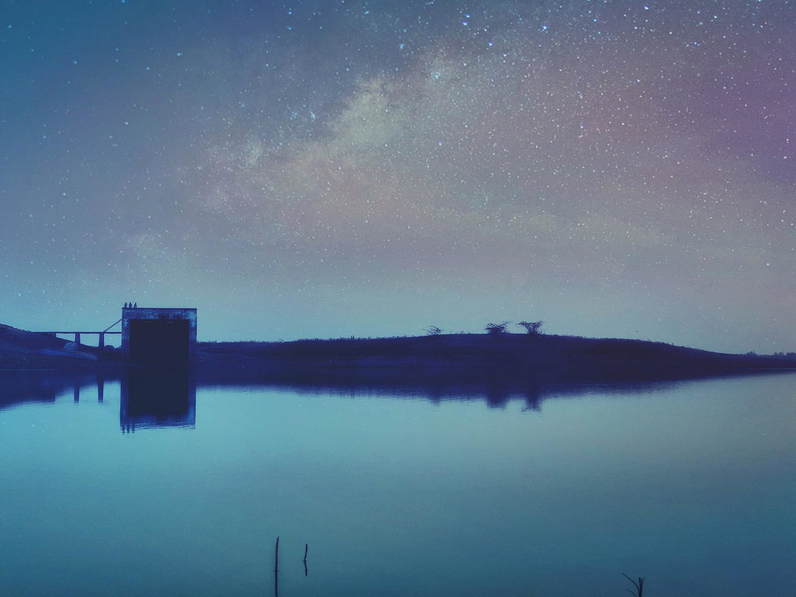 Blue body of water under light starry sky.