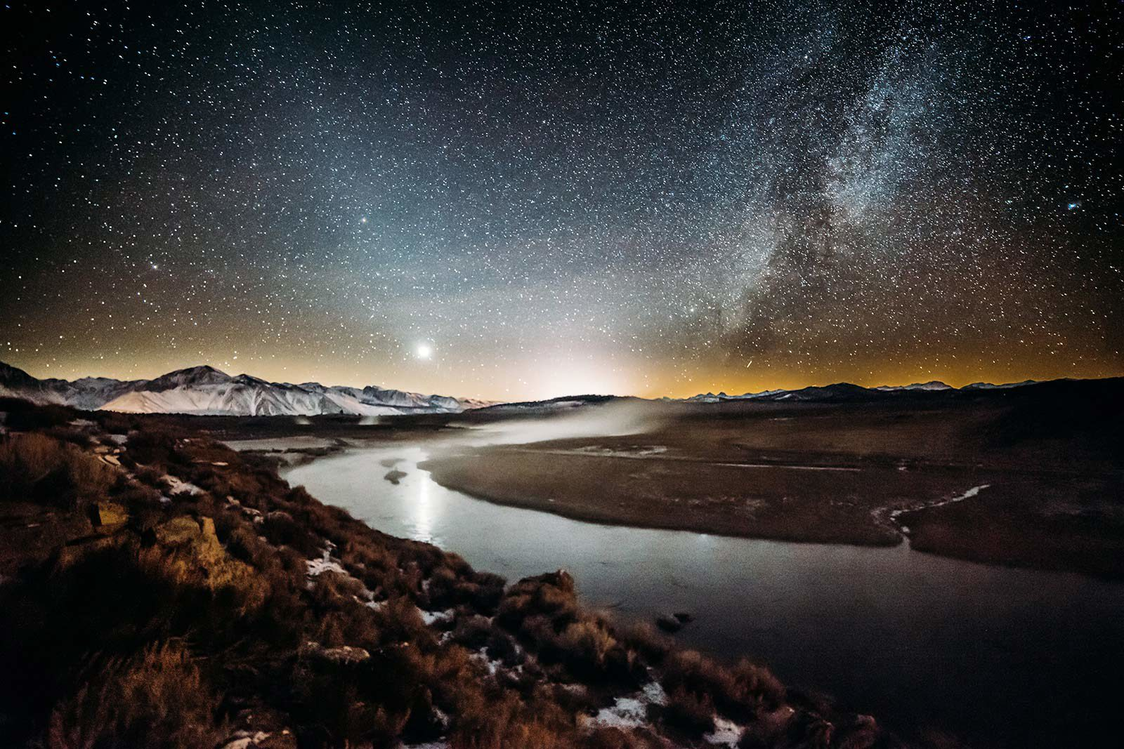 View of winding river and snowy mountains under starry sky.