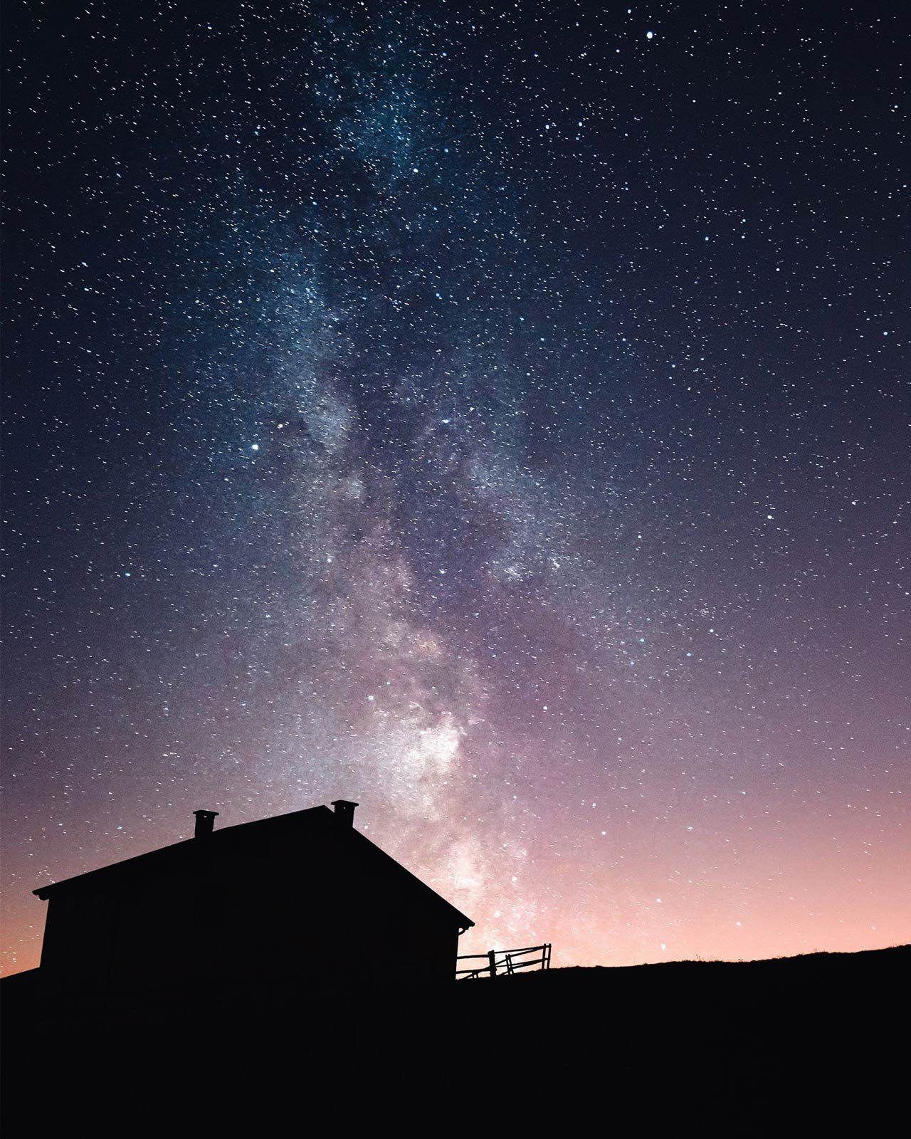 Silhouette of house under starry sky and milky way.
