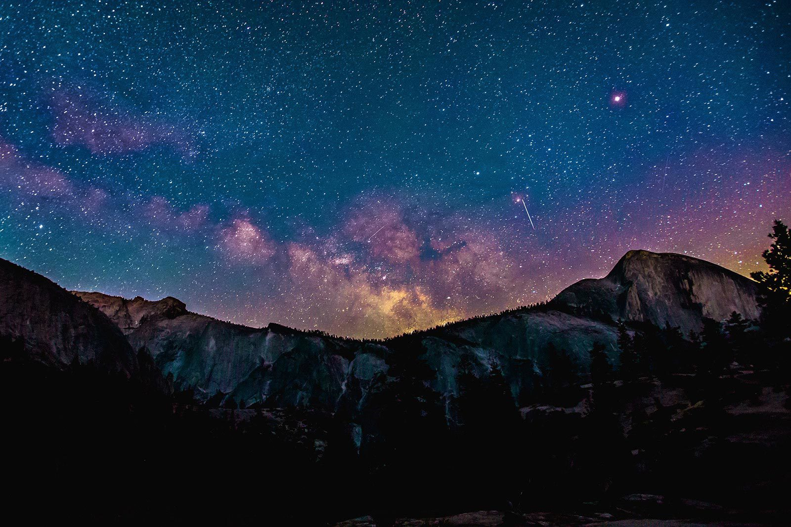 View of mountain under starry blue and purple sky.