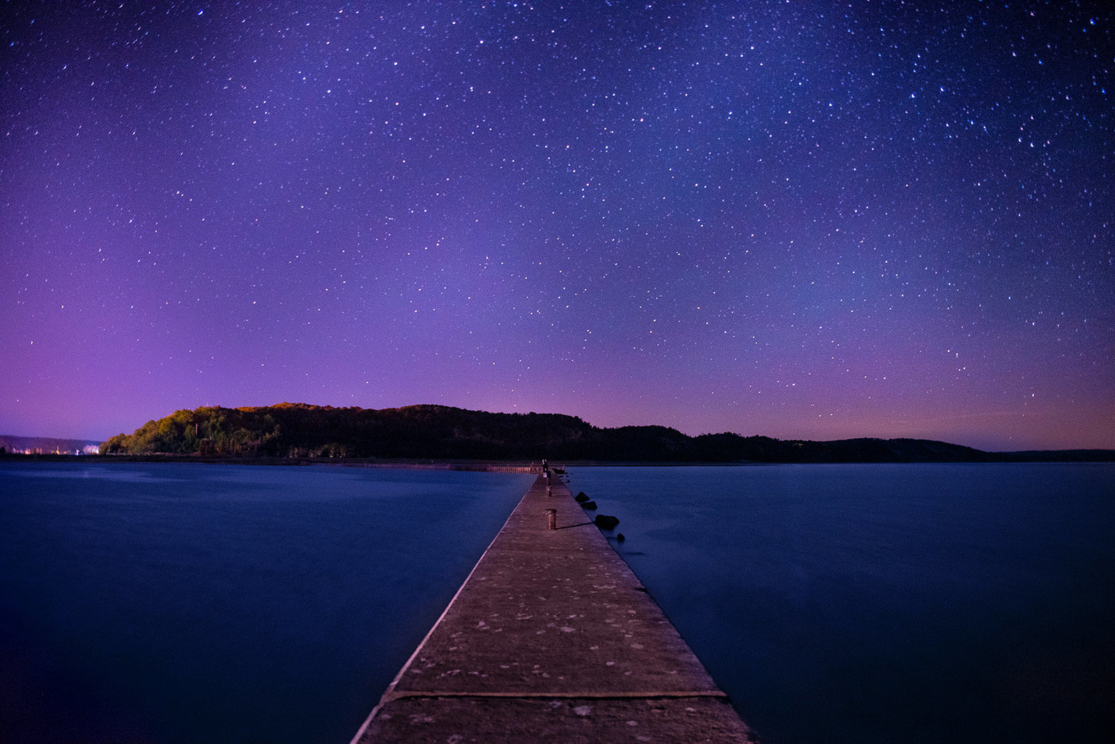 Long cement walkway over still blue water leading to island under blue and purple starry sky.