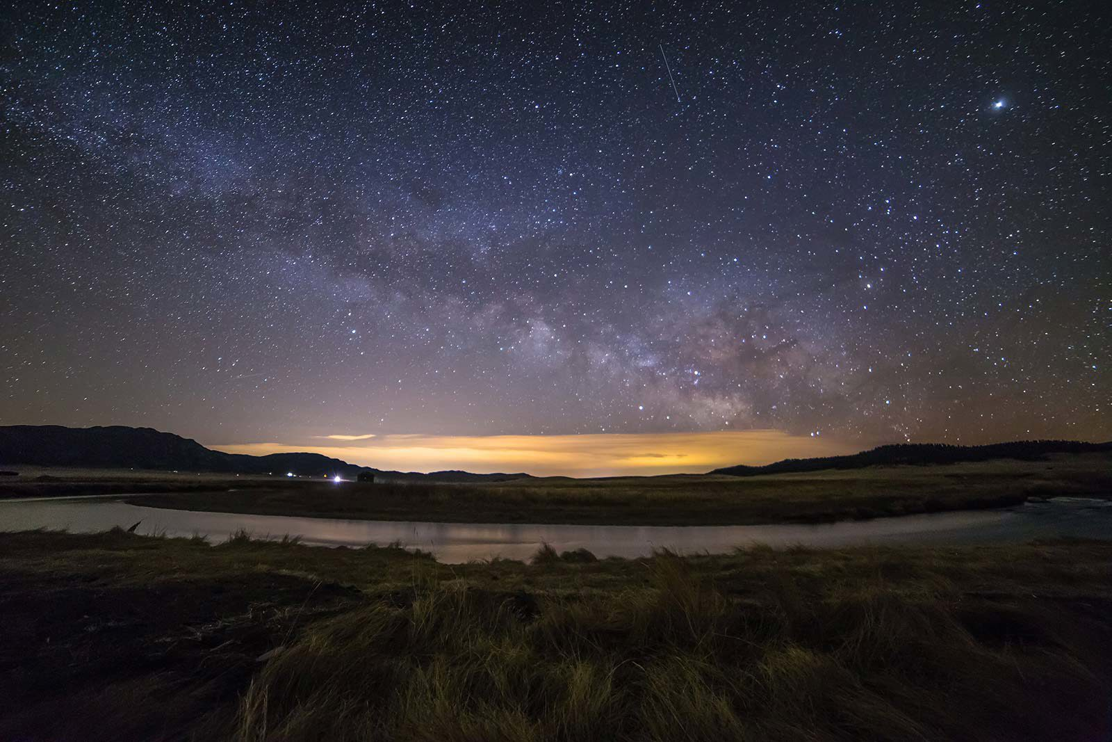 Field and lake under starry sky with sunrise in distance.