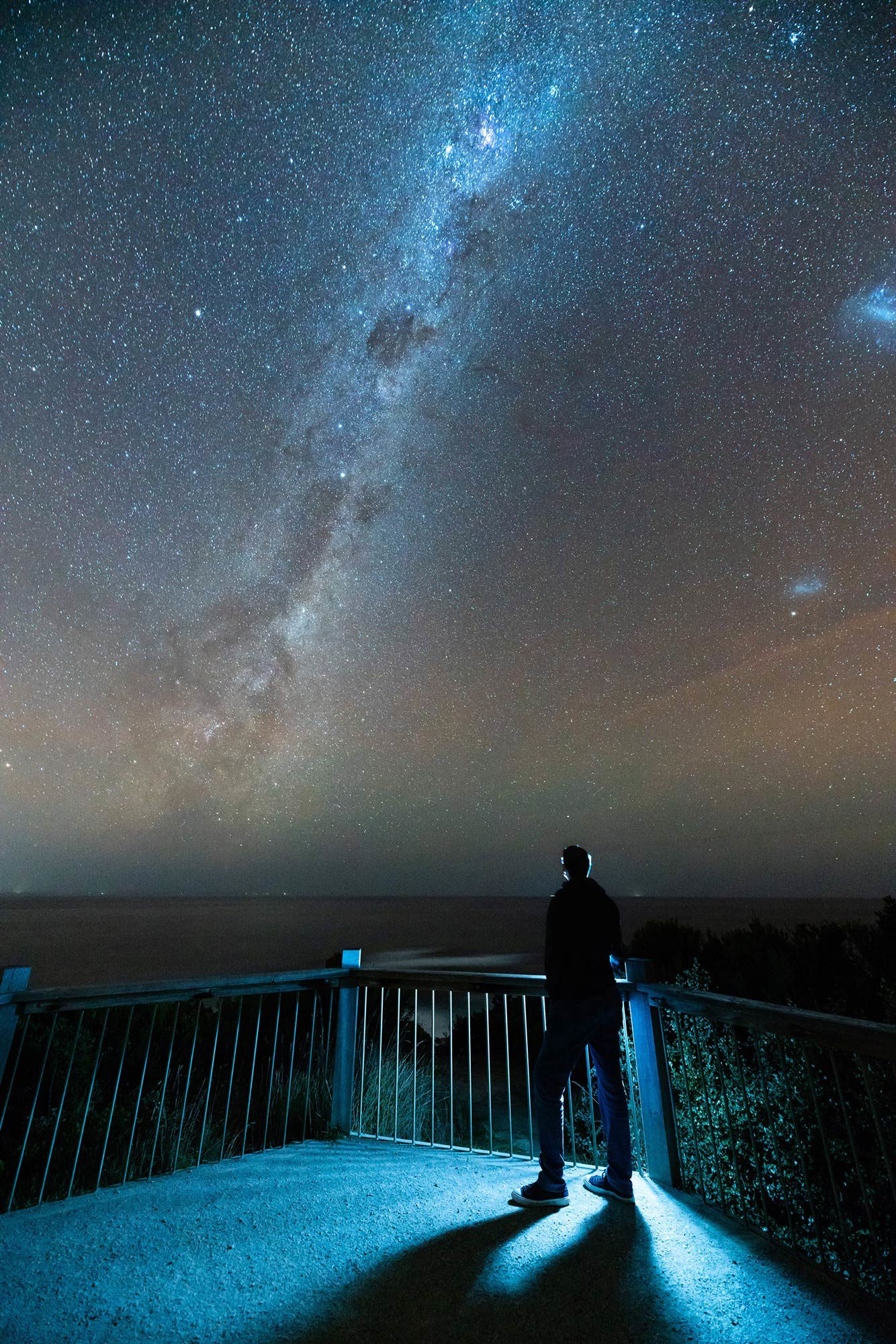 Man standing on balcony looking at stars.