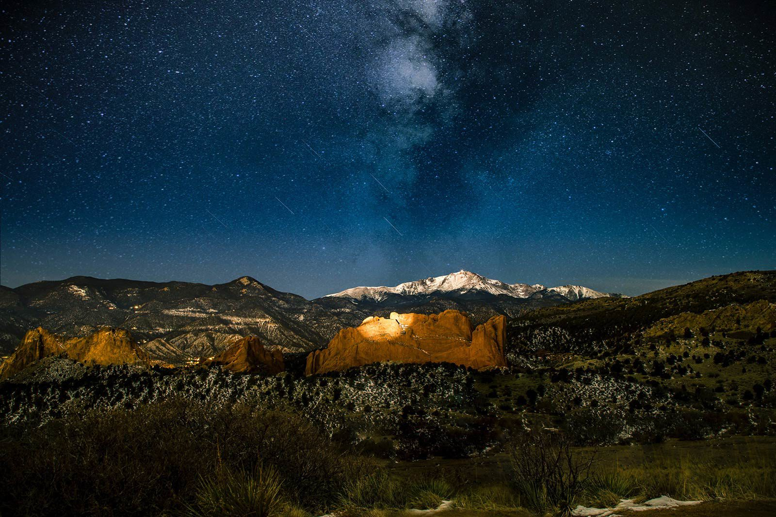 View of snow-capped mountains under dark blue starry sky.