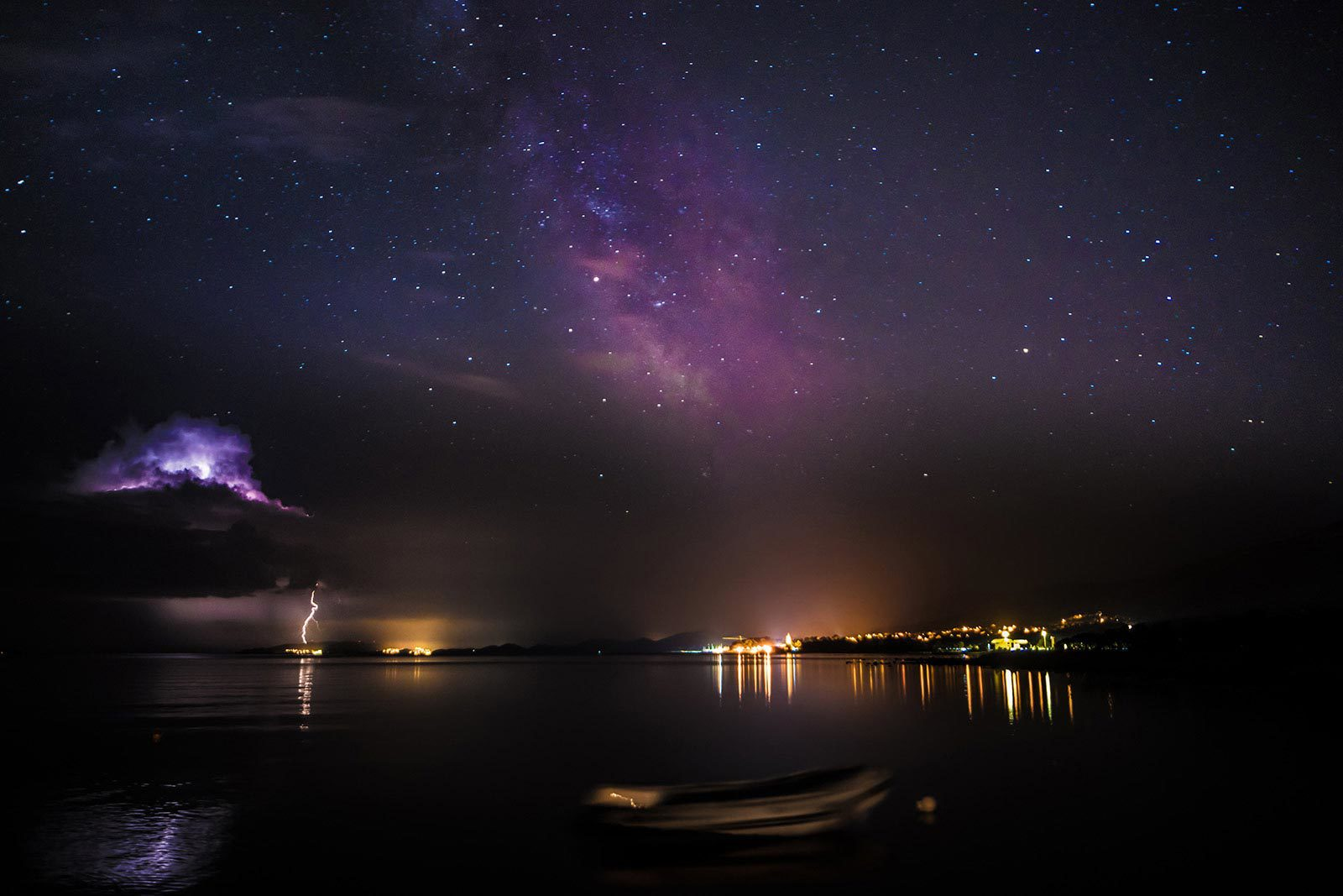 View of lake with city in distance, purple starry sky and lightning in distance.