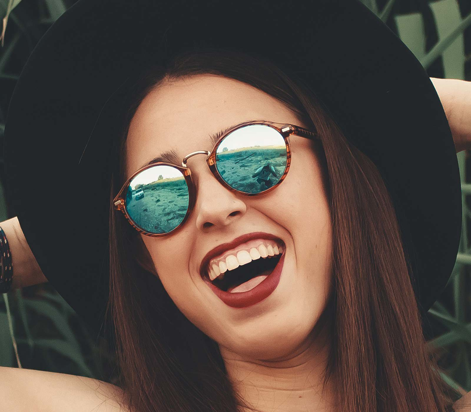 Close up of woman in brimmed hat and blue sunglasses laughing with hands at back of head.