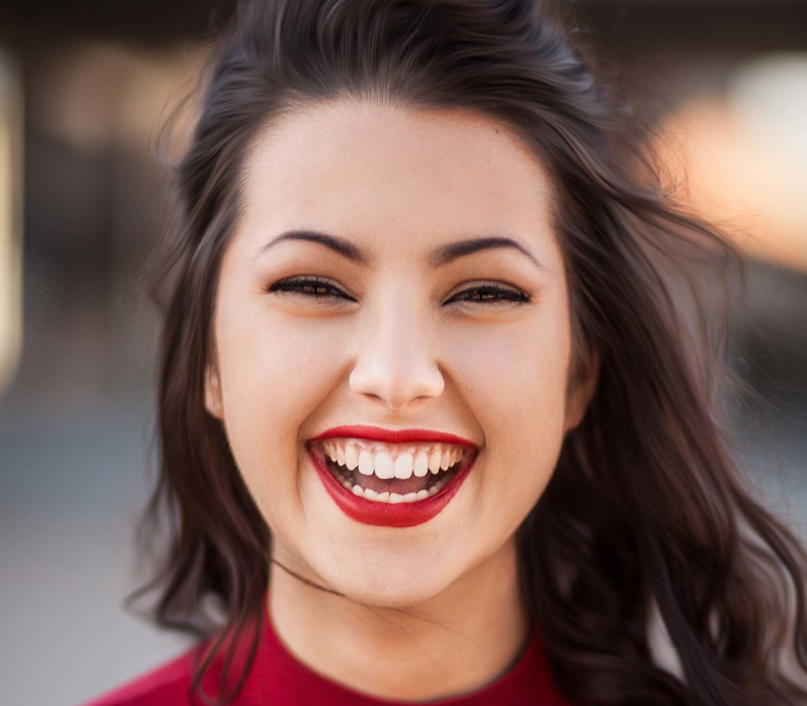 Close up of woman in red lipstick laughing into camera.
