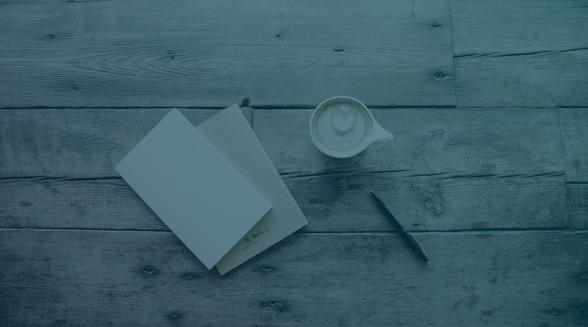 Blue-toned image of wooden table with notebook, pen and coffee.