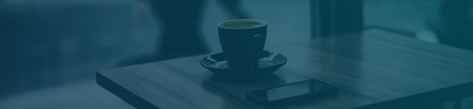 Blue-toned image of table with coffee and cellphone.