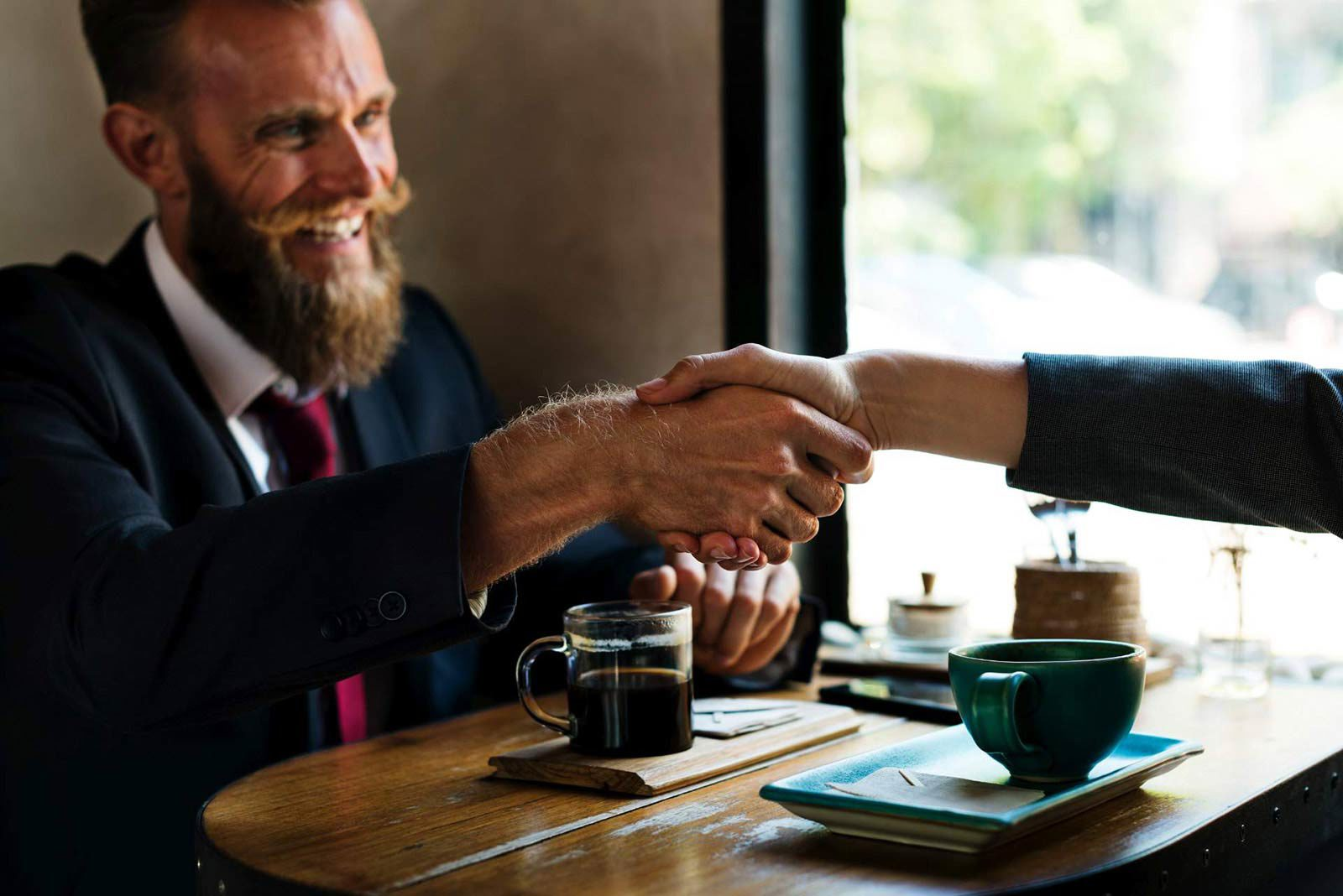 Man in suit with beard smiling shaking person's hand over coffee.