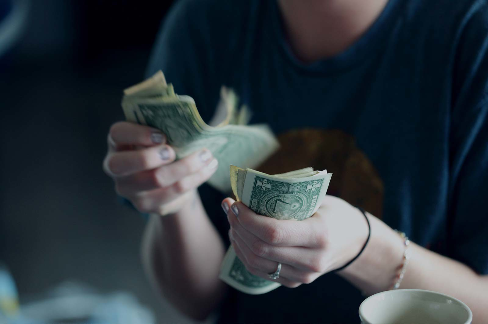 Closeup of person's hand counting American dollar bills.