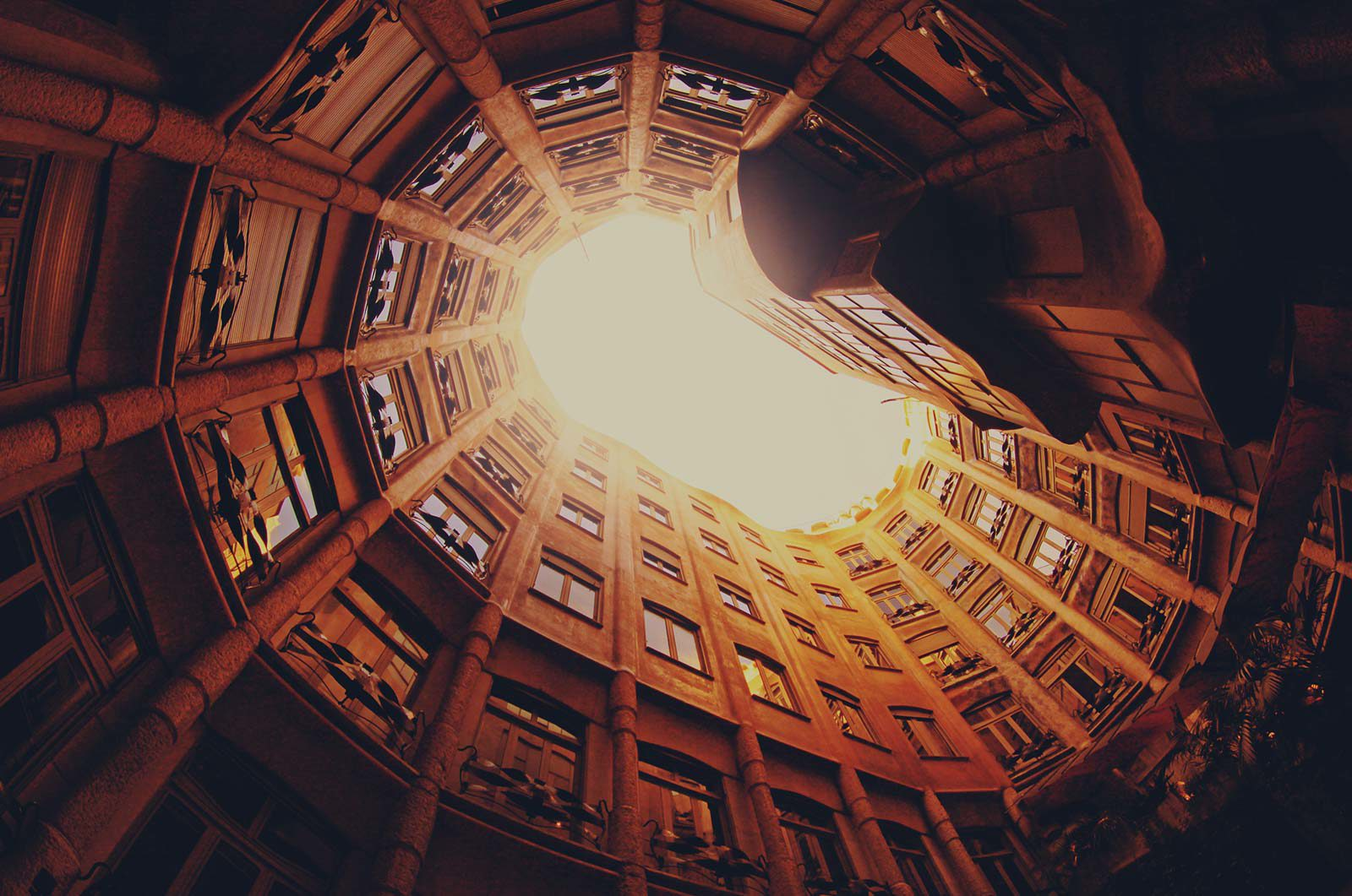 View looking up of an orange, circular building with various rooms.