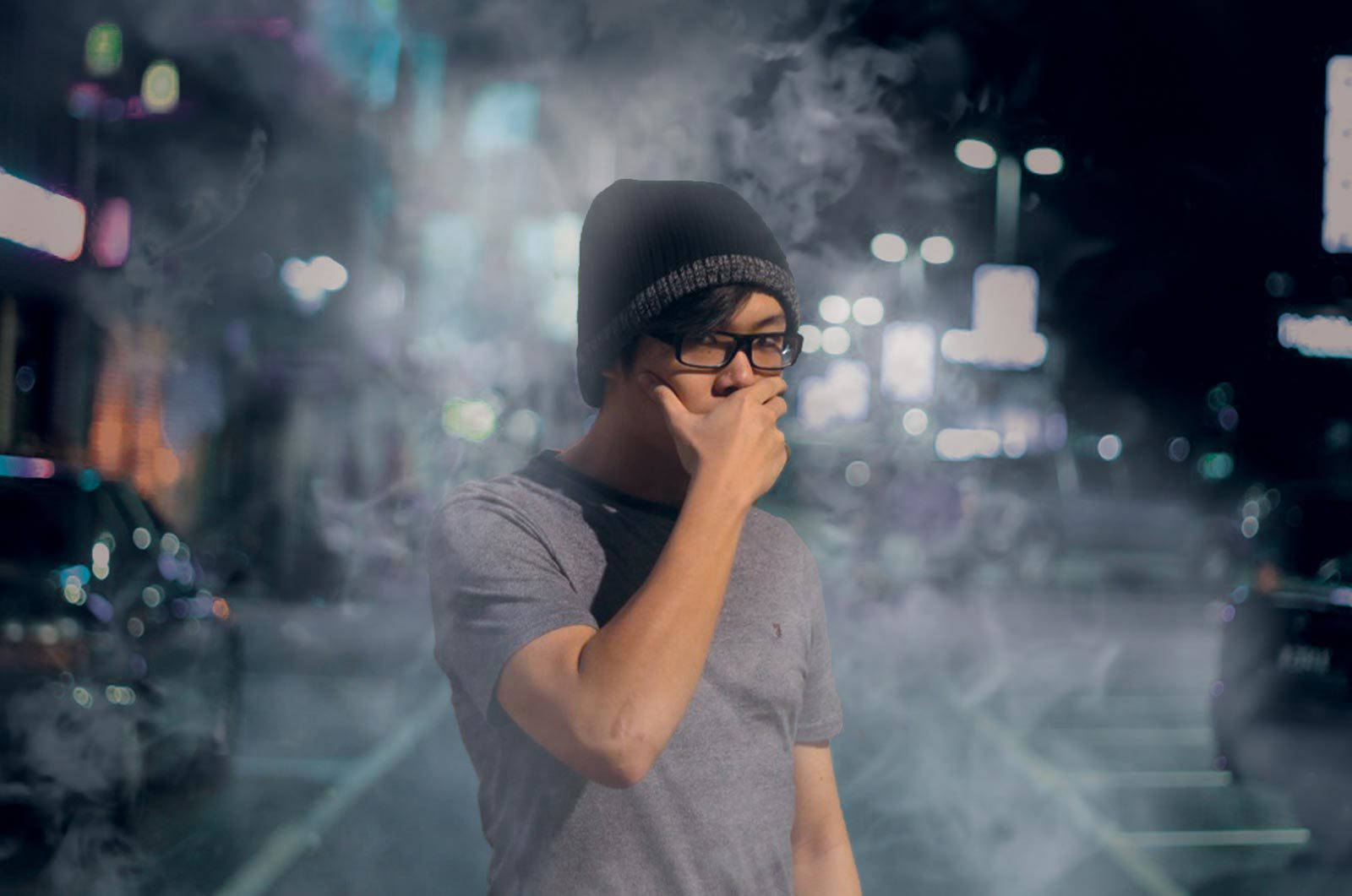 Man with hand over his mouth standing in street surrounded by smoke.