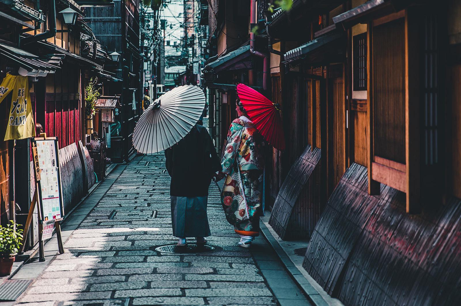 Two women with parasols walking down backstreet in Asia.
