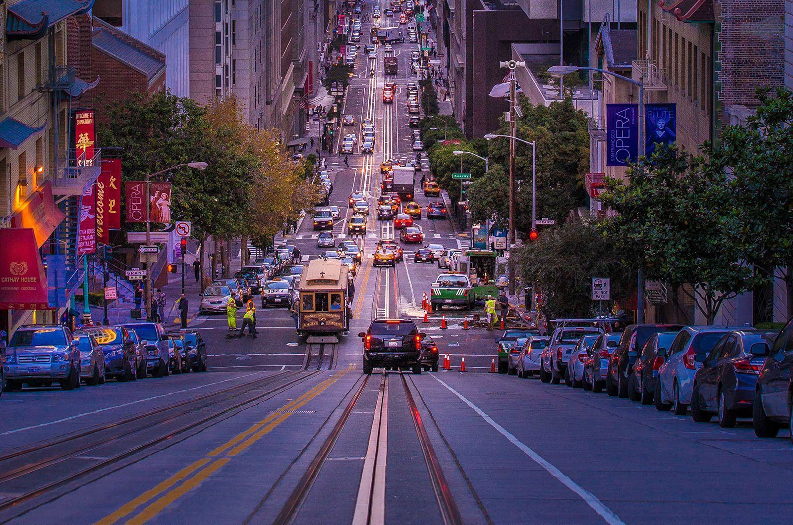 View looking down at large hill from centre of busy road with streetcar approaching.