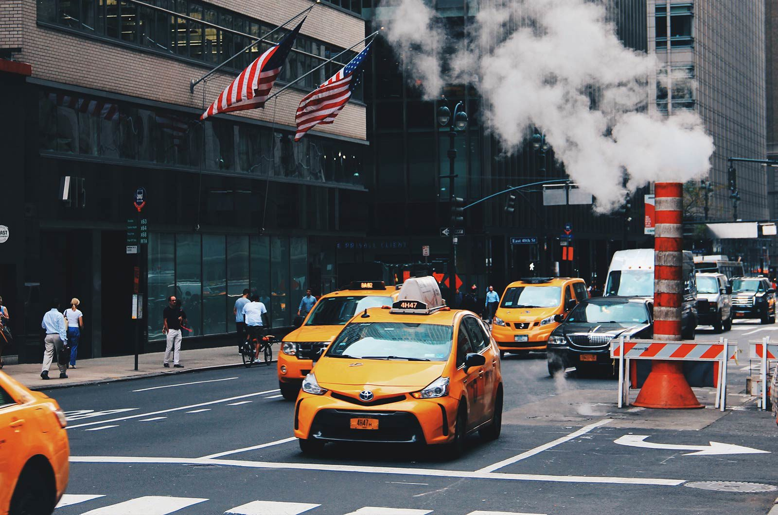 Taxis on street next to smoking construction and American flags hanging from buildings.