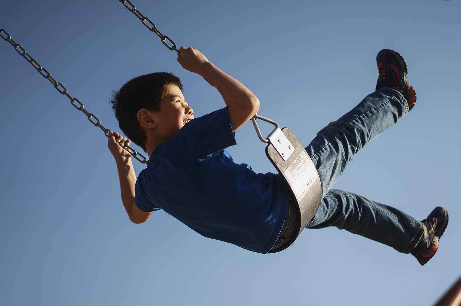 Child laughing on swing.