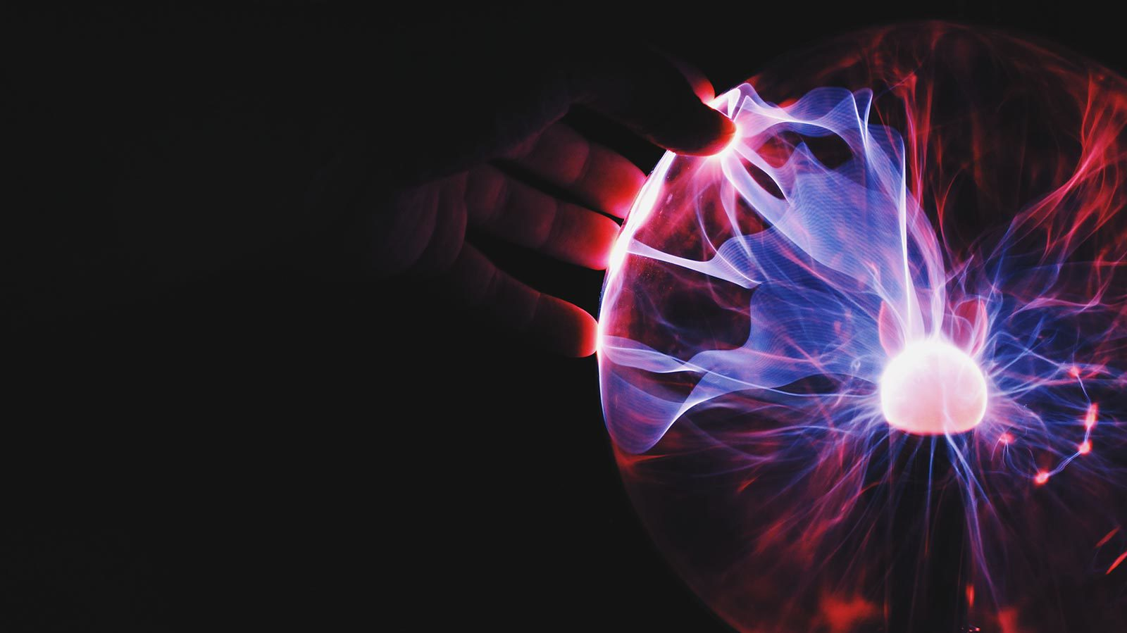 Hand touching red and purple plasma ball.