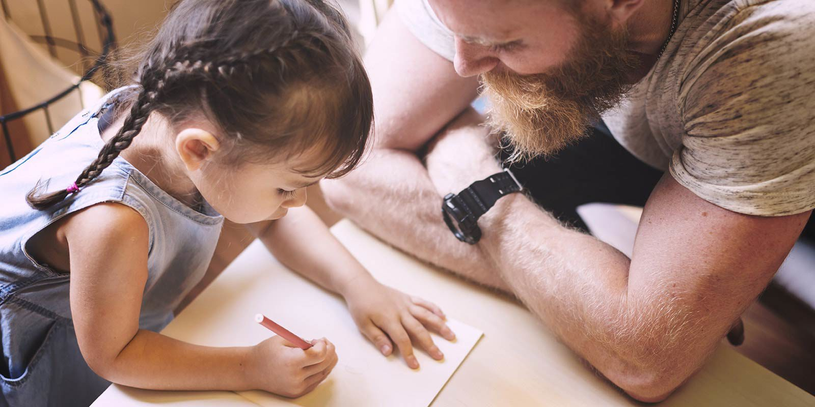 Man watching young girl draw with pencil and paper.