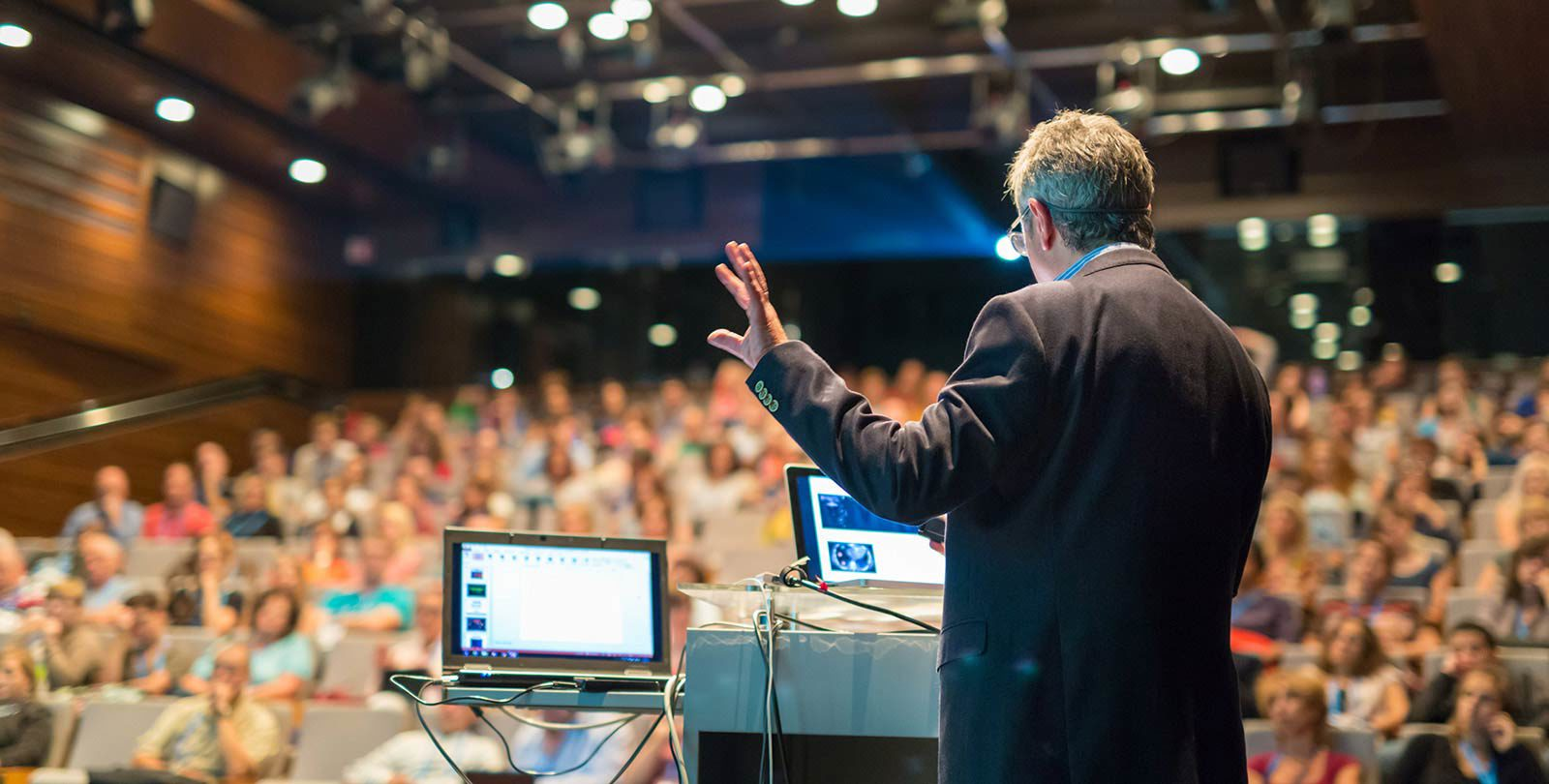 Man with hand in air looking at two laptops talking to full lecture hall.