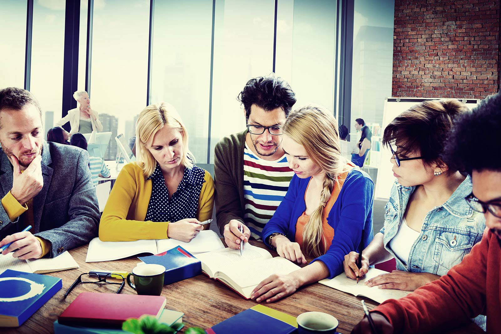 Six people sitting at table looking at notebook.