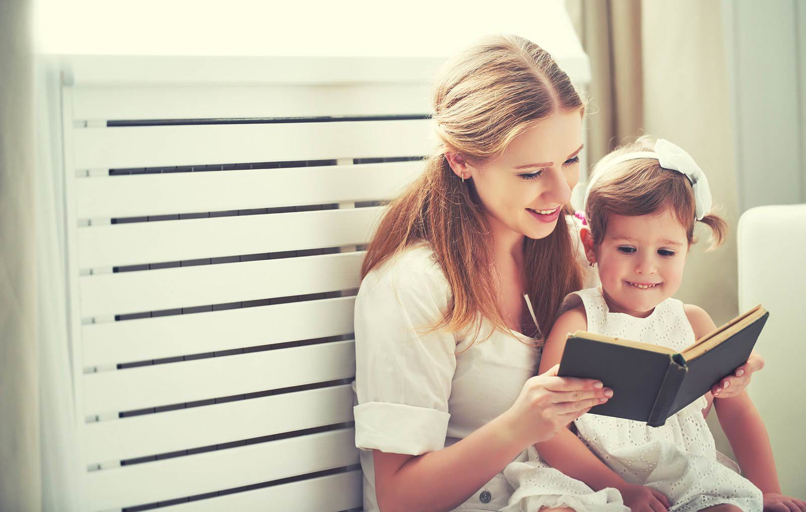 Woman sitting with small child reading her a book.