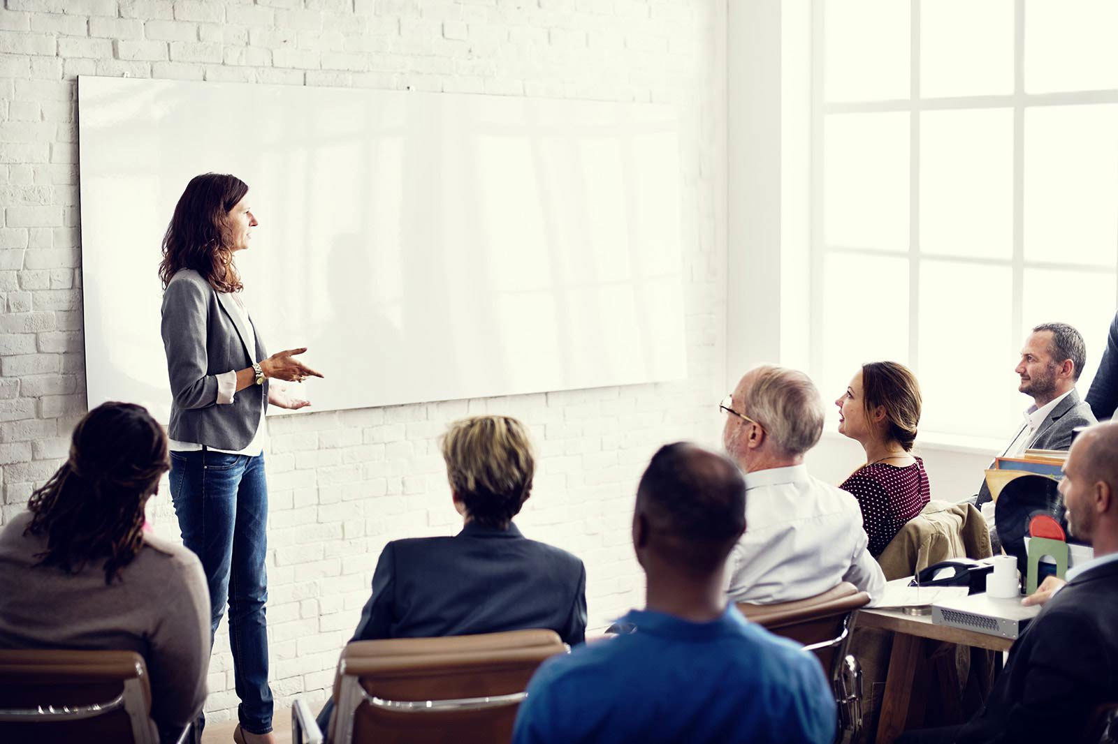 Woman standing in front of whiteboard presenting to group in chairs.