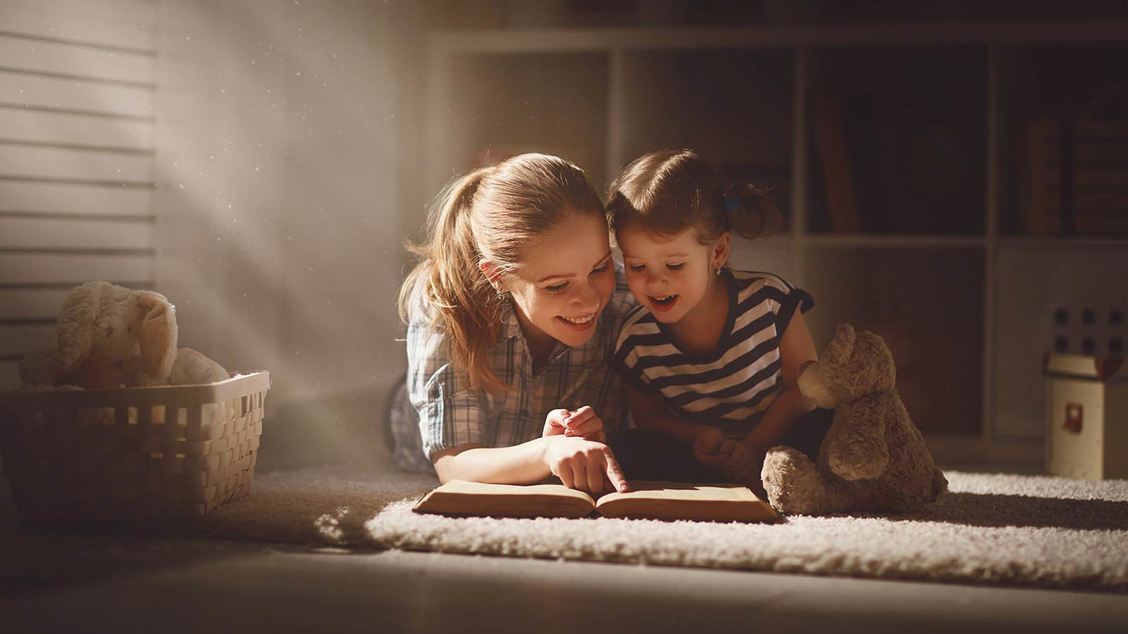 Woman and young girl lying on carpet with teddy bear reading book.