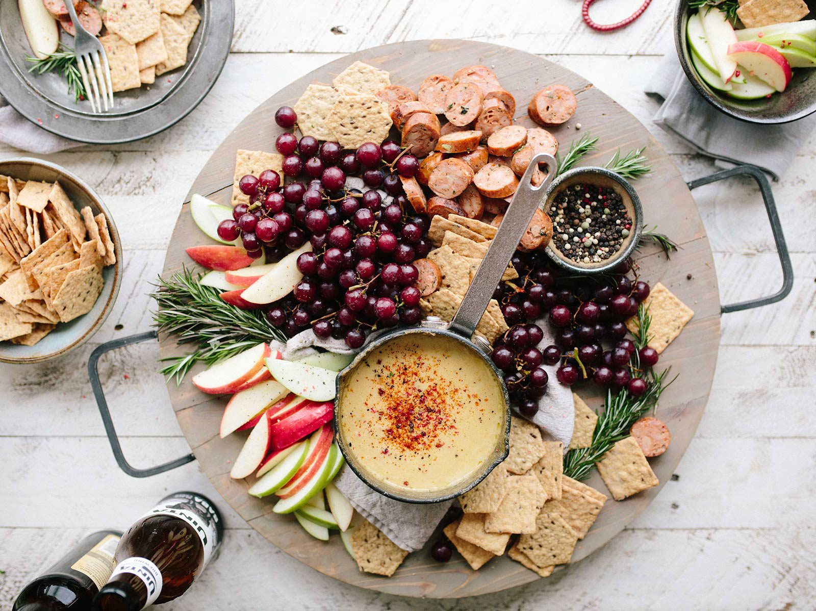 Platter of cheese, crackers, apples, meat and small berries on table with bowl of crackers, fruit and bottled drinks.