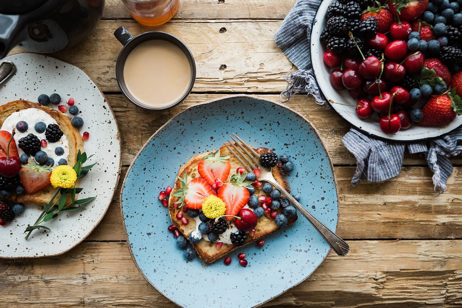 Toast with strawberries, blueberries, blackberries, and pomegranate seeds on plate next to bowl of berries, toast and coffee.