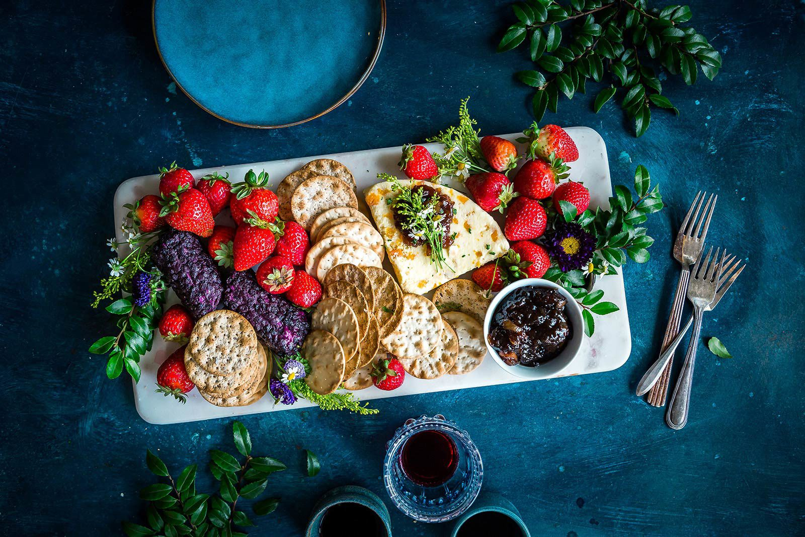 Platter of bread, crackers, strawberries and preserves with leaves and flowers on blue table.