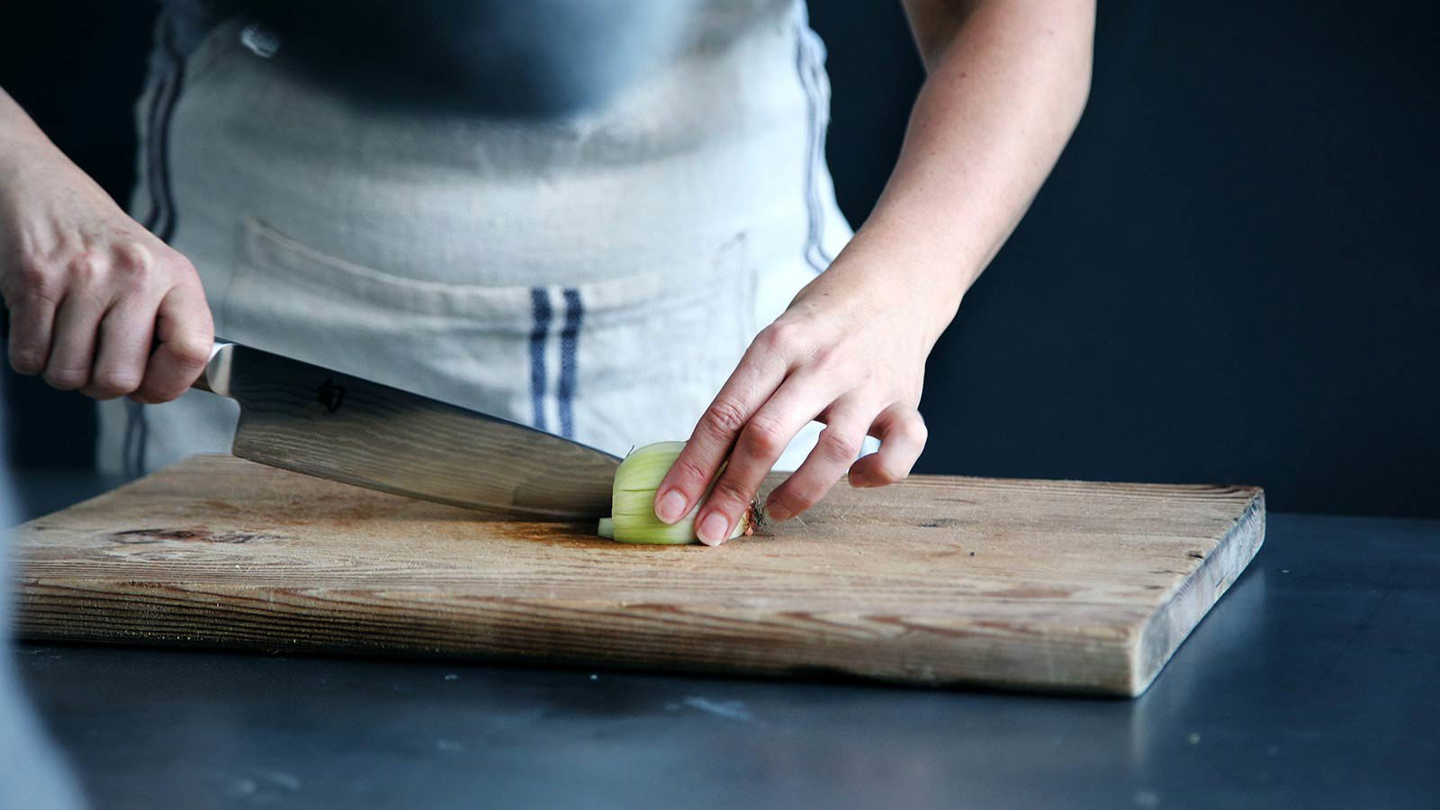 Person in apron cutting onion on cutting board.