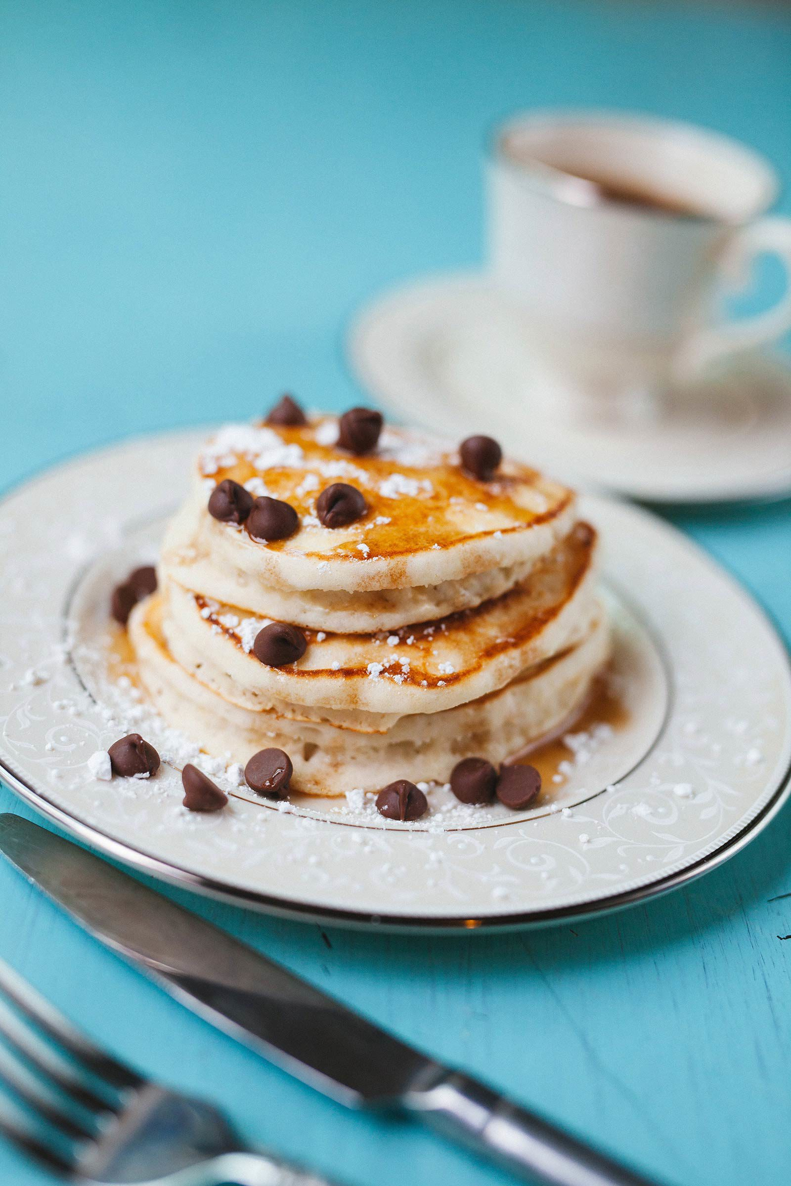 Stack of pancakes with chocolate chips and powdered sugar on blue table next to utensils and coffee.
