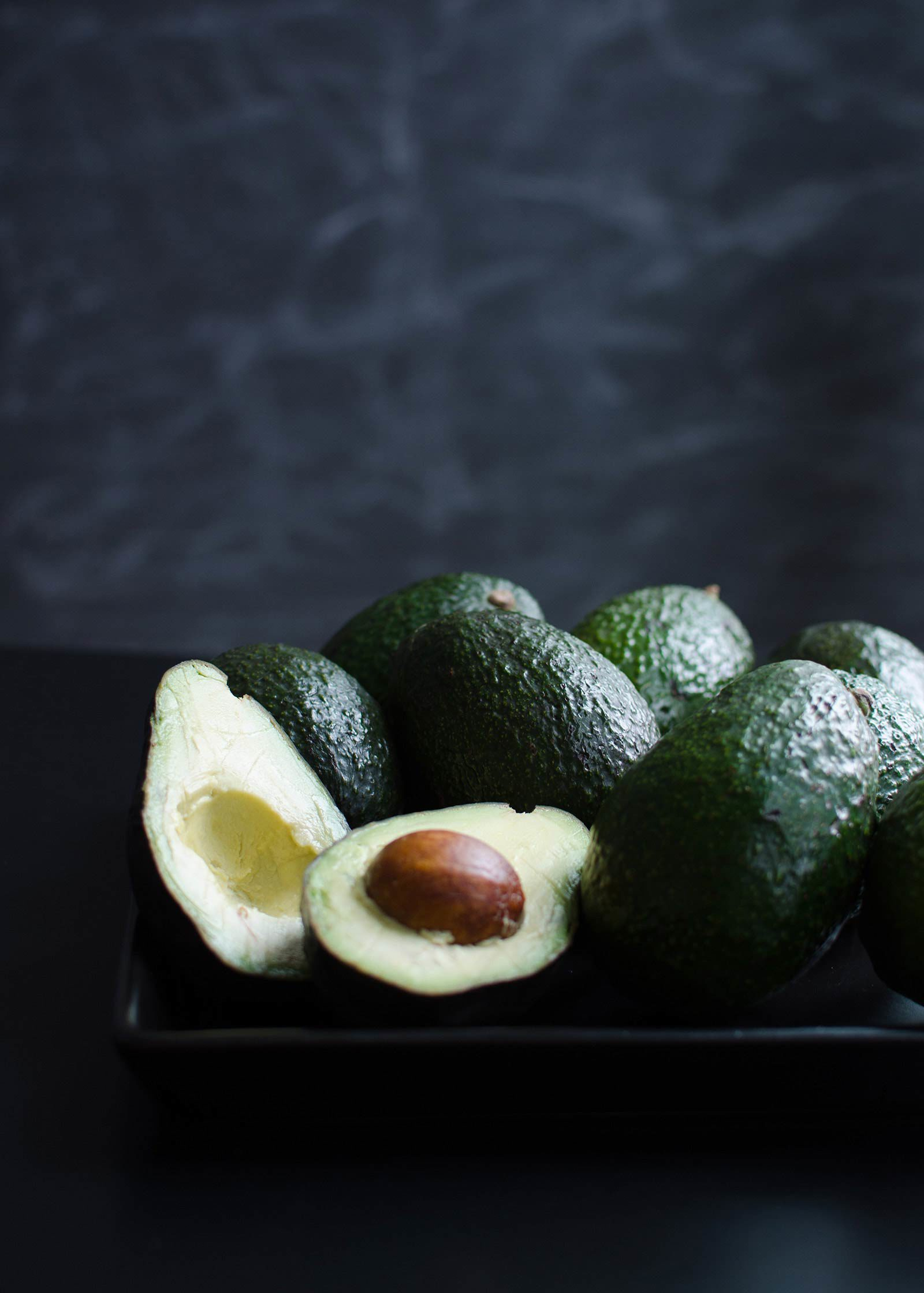 Array of avocados sitting on black plate, one cut in half.