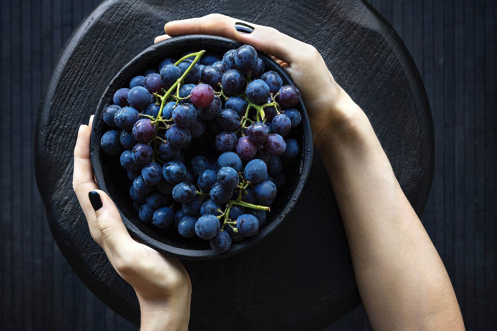 Person with black nail polish holding bowl of blue wine grapes.