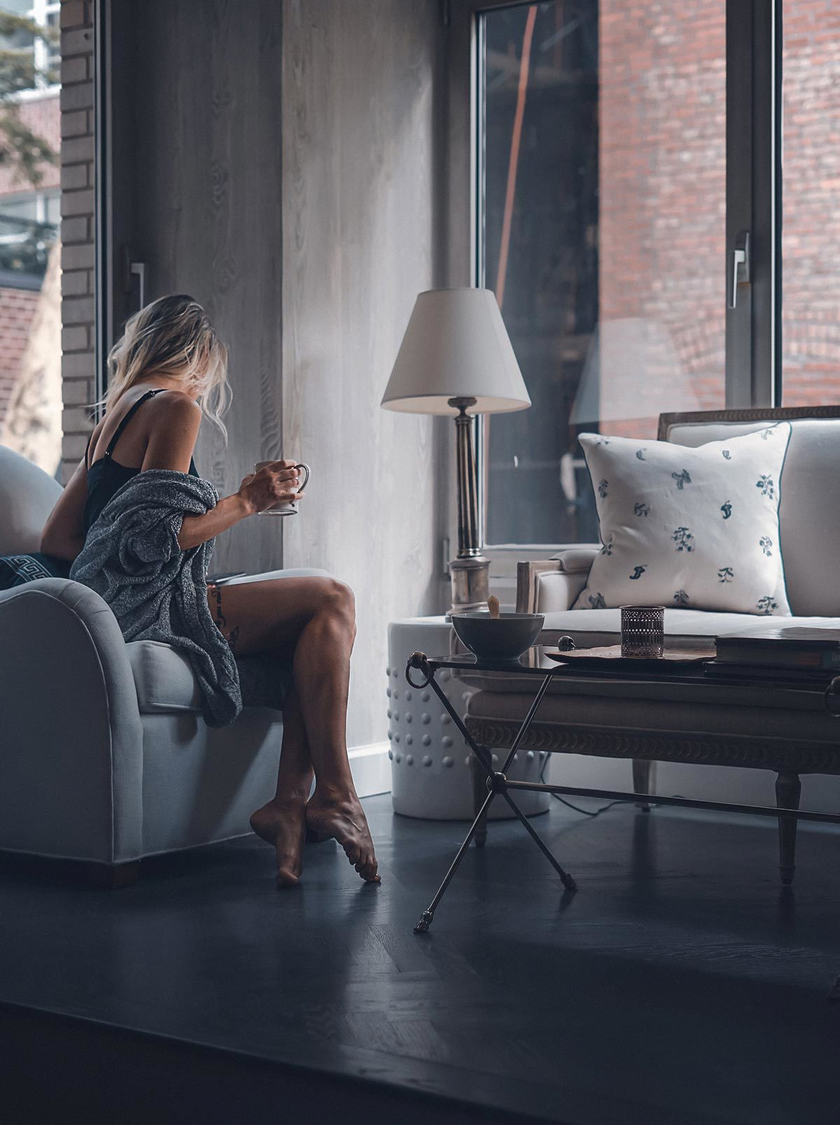 Woman sitting on sofa turned away holding coffee.