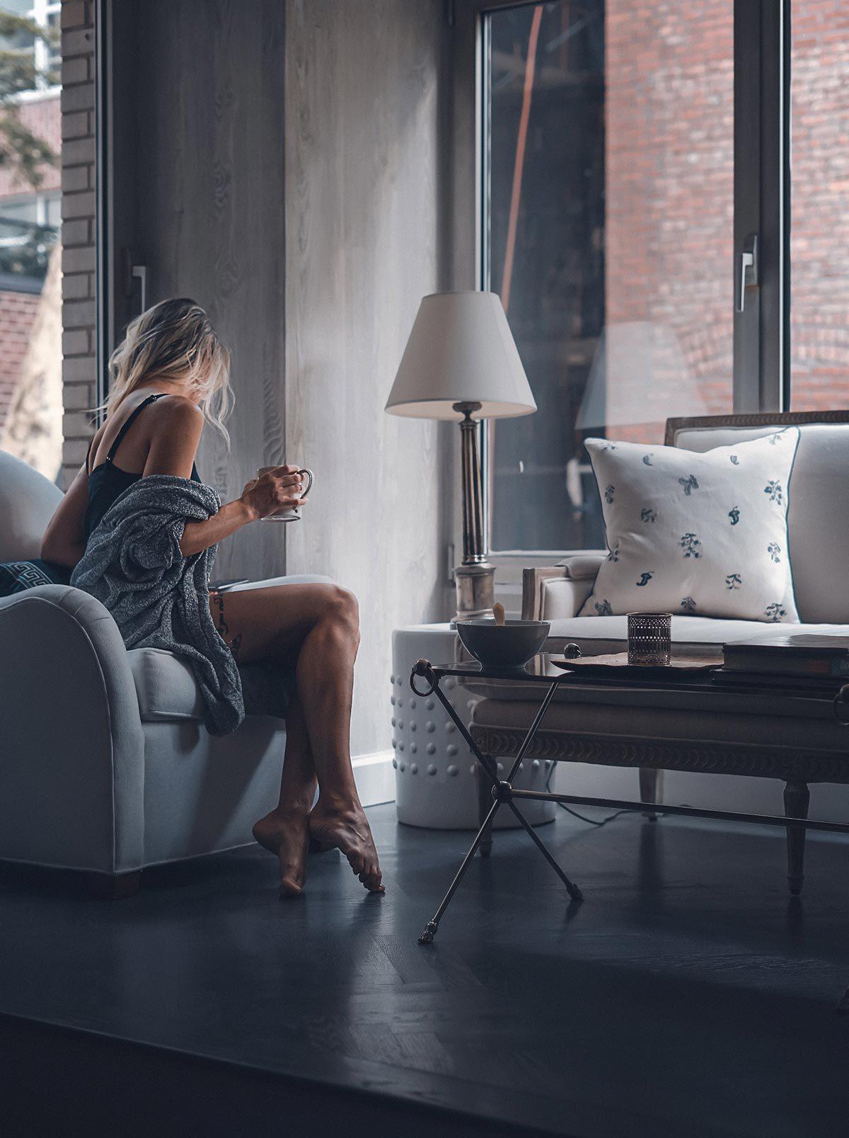 Woman sitting on sofa turned away holding coffee.