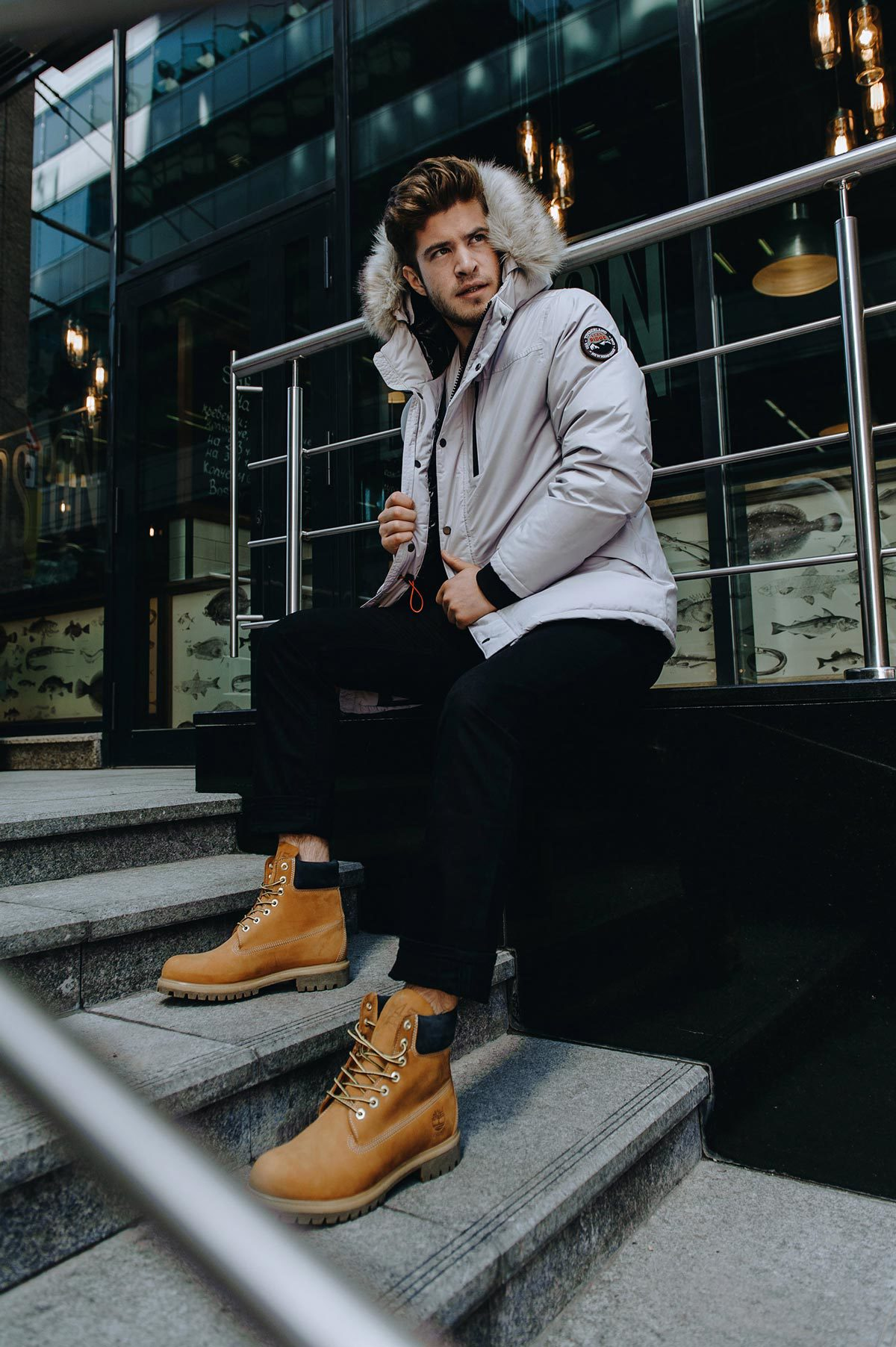 Man in winter coat and boots posing on staircase outside glass building.